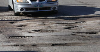 A motorist has little choice but to drive through this cluster of potholes at Ferry Road and Ness Avenue Tuesday.