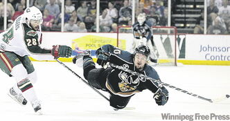 Manitoba's Michael Grabner (right) is taken down by the Houston's Brandon Rogers.