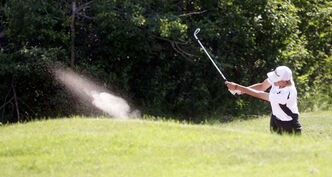 Travis Fredborg drives his ball out of a sand trap during the third round.