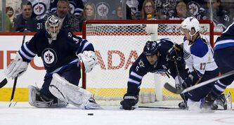 Jets goaltender Ondrej Pavelec tries to get back in position as Winnipeg defenceman Mark Stuart and St. Louis centre Vladimir Sobotka scramble for the puck in the second period. The Jets lost 2-1.