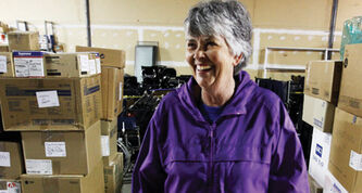 International HOPE Canada founder Phyllis Reader stands amid a warehouse full of medical supplies and equipment.