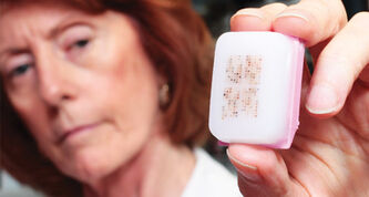 Dr. Leigh Murphy holds a paraffin block containing breast cancer tissue.