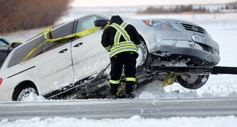 A tow truck operator secures the van in the ditch on the Perimeter Highway.