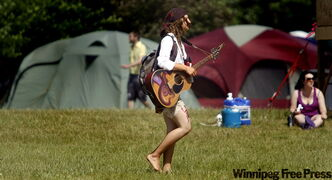 Carlen  Malinowski strolls through the Winnipeg Folk Festival's official campsite  Thursday  afternoon with guitar at the ready.