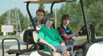 Nate (Nick Serino), at the wheel, Riley (Reece Moffett) in the passenger seat, and Adam (Jackson Martin) in the back are shown in a scene from the film