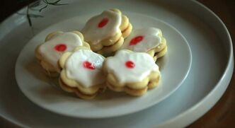 Imperial cookies like the ones above are sandwiched with jam, topped with white icing and decorated with a small piece of cherry.
