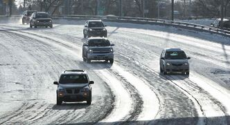 Vehicles make their way over the Norwood Bridge along roads covered in ice Sunday morning.