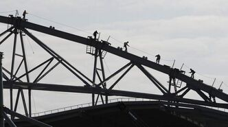 Workers at  Investors Group Field make their way along the stadium cover beams Tuesday. High winds have impeded construction of the new stadium, and last night wind knocked over a small wall.