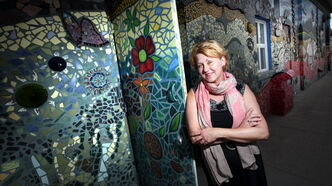 Red Road Lodge executive director Beverly Burkard poses with a giant mosaic mural decorating the west wall of The Red Road Lodge, one of the featured buildings in Doors Open Winnipeg, a free event happening this weekend.
