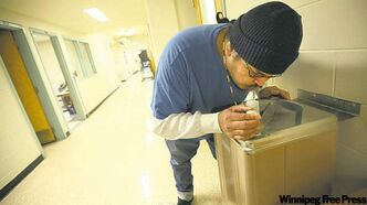 Stony Mountain inmate, Fabian Twohearts grabs a drink from a hallway fountain in the prison school.