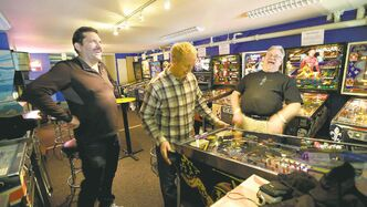 Out-of-state visitors Jeff Goldsmith, left, Jim Lindquist, center, and Dave Socha, right, play the PIN BOT pinball machine, which was released in 1986, as they visit the Seattle Pinball Museum in Seattle.