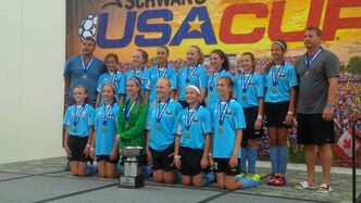 The Phoenix U12 developmental girls' soccer team celebrates its gold-medal win at the Schwan's USA Cup in Blaine, Minnesota. The team clinched the win with a 2-1 win over Minnesota's NSSA Blue Crew on July 19.  Back row: Gian Paolucci (coach), Jenna Kunkel, Neely Hammerberg, Madison Loewen, Callie Kjarsgaard, Imogen Bigras, Eryn Sitar, Camilla Paolucci, and John Hudohmet (coach). Front row: Holly Johnson, Trinity Gowen, Brylin Shuttleworth, Amelia Rheubottom, Sabrina Frick, and Megan Hudohmet.