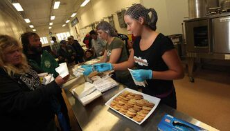 Reese Precourt hands out cookies to patrons Friday at the Lighthouse Mission's soup kitchen. Precourt baked cookies and donated the money towards the kitchen's renovations.