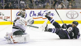 TREVOR HAGAN / WINNIPEG FREE PRESSMinnesota Wild goalie Niklas Backstrom keeps his eye on the airborne puck as Jets� Blake Wheeler takes a spill in front of him in the second period Saturday.