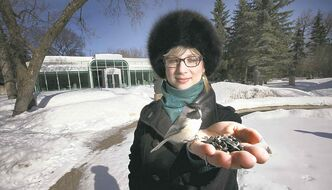 Lara Ciekiewicz lures birds with a handful of sunflower seeds at the Leo Mol Sculpture Garden.
