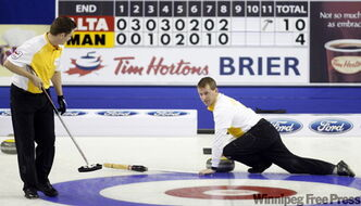 Manitoba second Rob Fowler looks on as skip Jeff Stoughton shoots his final rock at the Tim Hortons Brier in Calgary on Sunday.  Manitoba lost to Alberta 10-4.