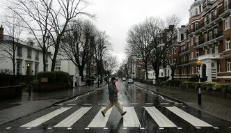 FILE - In this file photo taken Feb. 16, 2010, a man walks on the zebra crossing made famous from the album cover of The Beatles' 'Abbey Road' in front of Abbey Road Studios, seen at left, in London. EMI Group Ltd., home of The Beatles, Coldplay and Katy Perry, is being sold in two parts for $4.1 billion. (AP Photo/Akira Suemori, File)