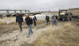 Farmers and supporters hold a rally  at the Portage Diversion near Portage la Prairie Monday. Farm machinery was parked in the spillway preventing the province from opening the gates.