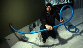 Ryan Black holds the hose he uses to get water from one of his neighbours. He has been without water since Jan. 31.