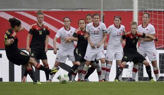 Canada's defence watches a free kick by Germany's Celia Okoyino Da Mbabi, left, during a friendly between Germany and Canada in Paderborn, Germany in June.