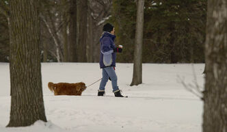 A woman walks her dog with a warm drink on Saturday morning in St. Vital Park.