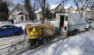 City crew heat a frozen water line running under a city street using a heavy duty battery connected to metal water pipes.