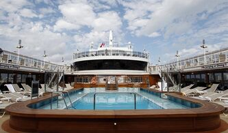 FILE - In this Sunday, Jan. 16, 2011 file photo, the pool area on deck 10 of the Queen Elizabeth docked at Port Everglades in Fort Lauderdale, Fla., More than three years since it arrived in its final port of Dubai, the storied cruise liner Queen Elizabeth 2 will soon be welcoming well-heeled guests once again - at least for a night. (AP Photo/Alan Diaz, File)