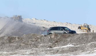 Dozers continue to pile snow at a dump site near Wilkes and the west Perimeter Highway Sunday.