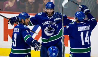 Kevin Bieksa, Ryan Kesler (centre) and Alex Burrows,who began their professional careers in Winnipeg, return to the MTS Centre Wednesday night.