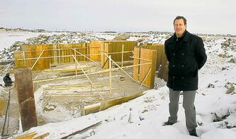 Spencer Curtis beside one of the first homes to be built at the development site.