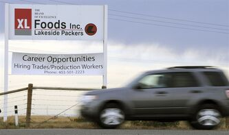 A vehicle passes the main entrance sign leaving XL Foods' Lakeside Packers plant in Brooks, Alta., on Oct. 1st, 2012. THE CANADIAN PRESS/Larry MacDougal