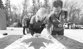 Ramona and Tim Turner sign a Canadian flag in support of the marathon victims.