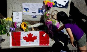 A woman leaves flowers at a makeshift memorial for former Vancouver Canucks hockey player Rick Rypien outside Rogers Arena in Vancouver, B.C., on Tuesday August 16, 2011. Rypien, who signed a one-year deal with the Winnipeg Jets in July, was found dead at his Alberta home on Monday. THE CANADIAN PRESS/Darryl Dyck