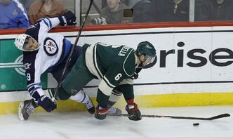 Minnesota Wild defenseman Marco Scandella (right) and Winnipeg Jets winger Evander Kane fall while chasing the puck during the first period of Sunday night's game in St. Paul, Minn.