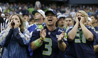 Seattle Seahawks fans yell during the first half of an NFL football game between the Seattle Seahawks and the San Francisco 49ers at CenturyLink Field, Sunday, Sept. 15, 2013, in Seattle. Fans were attempting to set a Guinness World Record for crowd noise at an athletic event during the game. (AP Photo/Elaine Thompson)