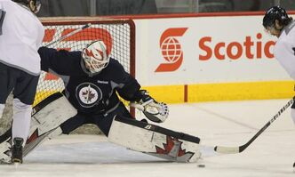 Winnipeg Jets goaltender Chris Mason (50) goes for full extension to stop a puck during practice at MTS Centre Tuesday morning.