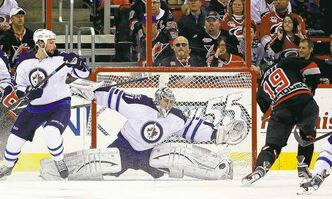 Jets goalie Ondrej Pavelec blocks a shot by the Canes' Jiri Tlusty (19) as the Jets' Zach Bogosian watches the play unfold.