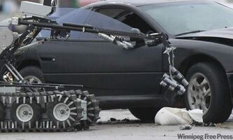 A Winnipeg Bomb Unit robot collects items it detonated after a suspicious package was seen in a vehicle involved in a  two-vehicle collision on Portage Avenue at Strathcona Street Monday morning that sent two to the hospital.