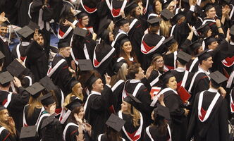 University of Winnipeg graduates wave to thank family and friends at the institution's June 2013 convocation.