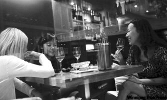 Patrons enjoy a bottle in a Chinese wine bar.