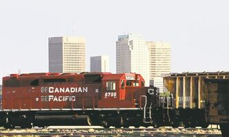 A CP train engine passes along the tracks at the CP Rail yards with downtown Winnipeg in the background.