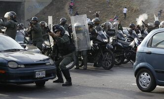 Riot police fire rubber bullets as demonstrators throw rocks against them during clashes after opposition supporters and students blocked a highway in the Altamira neighborhood in Caracas, Venezuela, Monday, April 15, 2013. National Guard troops fired tear gas and plastic bullets to disperse students protesting the official results in Venezuela's disputed presidential election.(AP Photo/Fernando Llano )
