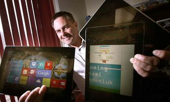 Joel Semeniuk brandishes fistfulls of portable devices. He spoke of changes in the software development world at a Winnipeg Conference Monday.