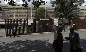 A journalist, left, walks with his camera outside Rome's tribunal and prosecutor's office, Friday, June 28, 2013. A Vatican official already under investigation in a purported money-laundering plot involving the Vatican bank was arrested Friday in a separate operation: Prosecutors allege he tried to bring 20 million euros ($26 million) in cash into Italy from Switzerland aboard an Italian government plane, his lawyer said. Monsignor Nunzio Scarano, a recently suspended accountant in one of the Vatican's main financial departments, is accused of fraud, corruption and slander stemming from the plot, which never got off the ground, attorney Silverio Sica told The Associated Press. (AP Photo/Alessandra Tarantino)