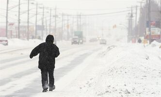 A man walks along a snow-covered Dundas Street in London, Ontario, Wednesday, February 2, 2011, after the area was hit by a winter blizzard overnight. Environment Canada says a snowstorm that's bearing down on Ontario will make itself felt in the Maritimes days later.THE CANADIAN PRESS/Dave Chidley