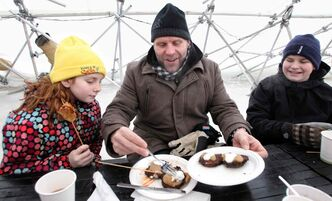 Kerry LeBlanc serves breakfast latkes to his daughter, Kwynn (left), and son, Karter, during brunch at the River Pop-up restaurant located on the Assiniboine River at The Forks.