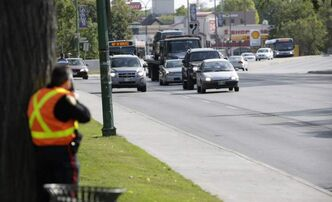 A Winnipeg police officer operates a speed trap on Osborne Street from behind a tree at the legislature.