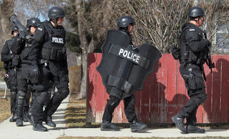 A city police Tactical team marches away from a house they raided.