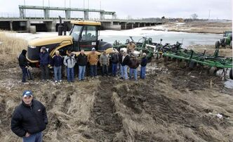 In the foreground, Joe Johnson, who has a farm on the west shore of the south basin of Lake Manitoba, along with other farmers and supporters held a rally at the Portage Diversion near Portage la Prairie Monday. They are upset about the outstanding compensation still owed to them for their losses in 2011.