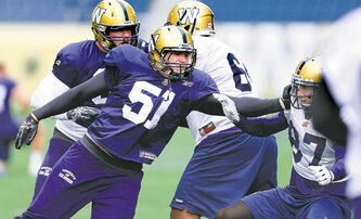Defensive end Jake Killeen (51) shoves receiver Rory Kohlert during the Blue Bombers' practice session Wednesday.